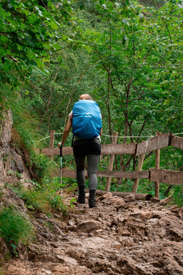 Wanderer auf Schotterweg beim Aufstieg zur Landsberger Hütte vom Vilsalpsee aus im Wald.