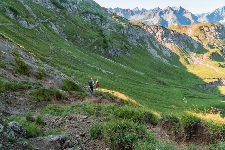 Wanderausrüstung: Wanderer auf Hüttenwanderung inAlpenlandschaft mit Fluss und Wiesen in den allgäuer Alpen.
