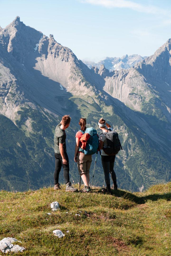 Auf dem WEg vom Tannheimer Tal zum Schrecksee: Wanderer, die das Bergpanorama geniessen. Wanderausrüstung mit Rucksack und Stöcken.