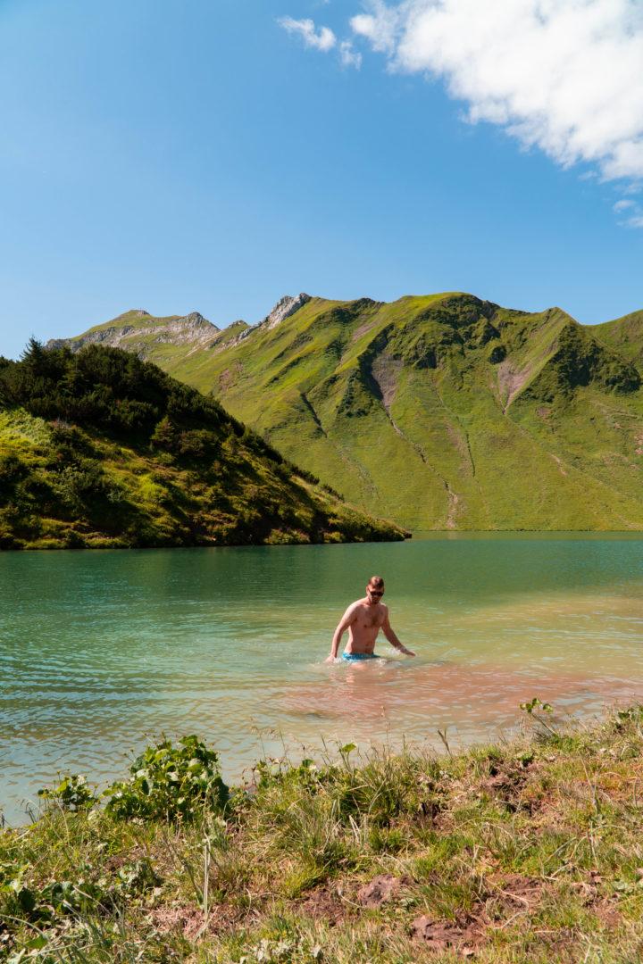 Badende im Bergsee, genannt Schrecksee mit kleiner Insel in der Mitte, im Grenzgebiet der österreichischen und allgäuer Alpen.
