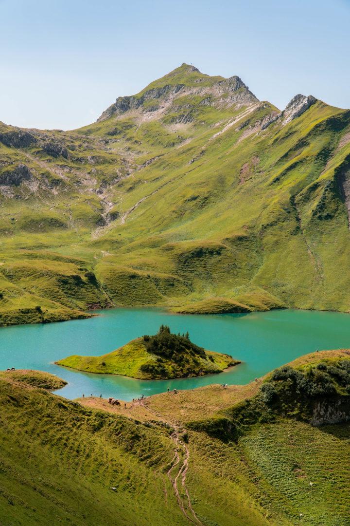 kristallblauer Bergsee, genannt Schrecksee mit kleiner Insel in der Mitte, im Grenzgebiet der österreichischen und allgäuer Alpen.