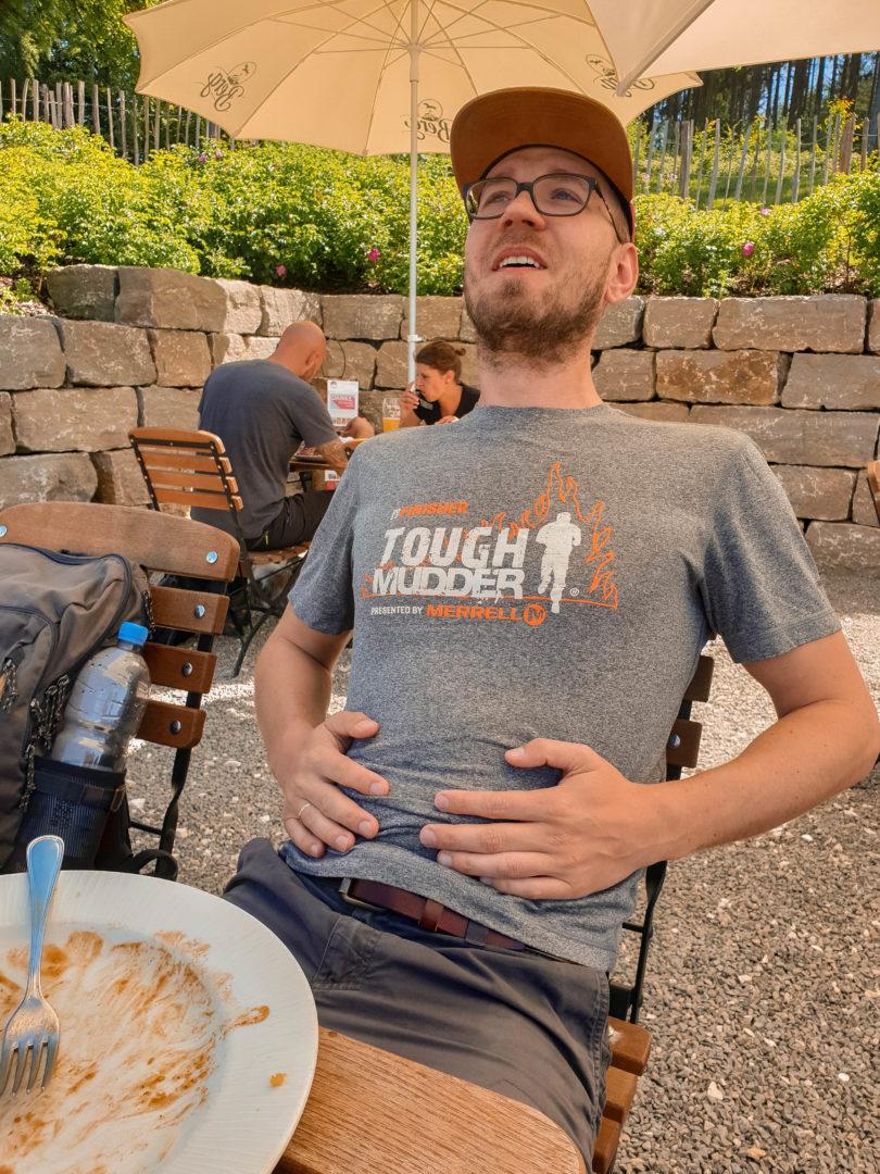 Mann, der sich den Bauch hält weil er in der Gaststätte zu viel gegessen hat.