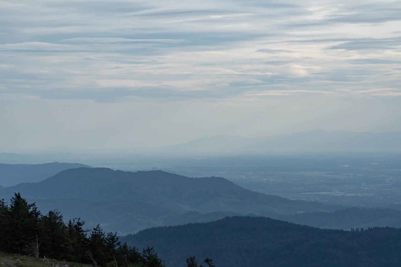 Blick über die Ausläufer des Schwarzwaldes von der Hornisgrinde aus. Der Himmel ist bewölkt, über den Bergen hängt Nebel, ein paar einzelne Sonnenstrahlen kommen durch.