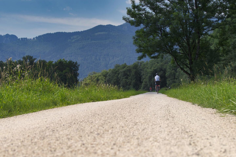 Radfahrer auf Schotterweg am Chiemsee.
