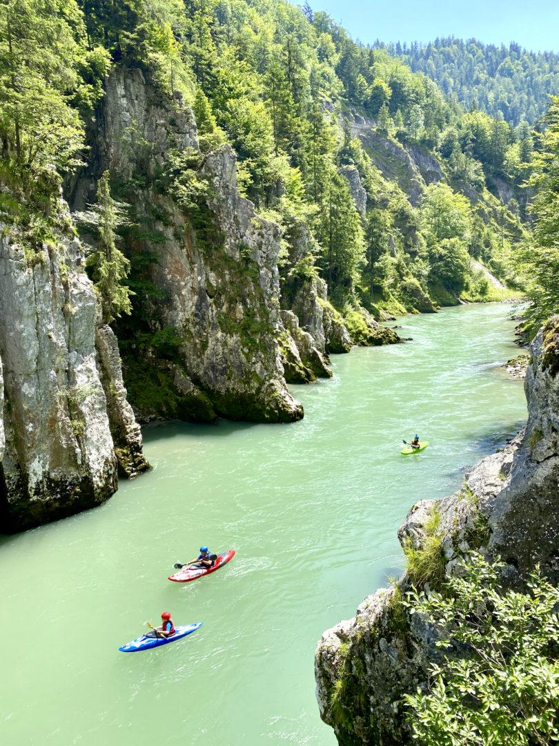 Wunderschöner Ausflug am Chiemsee: Der Schmugglerweg durch die Entenbucht. Klares Wasser fliesst durch einen Canyon, einige Kayakfahrer sind zu sehen.