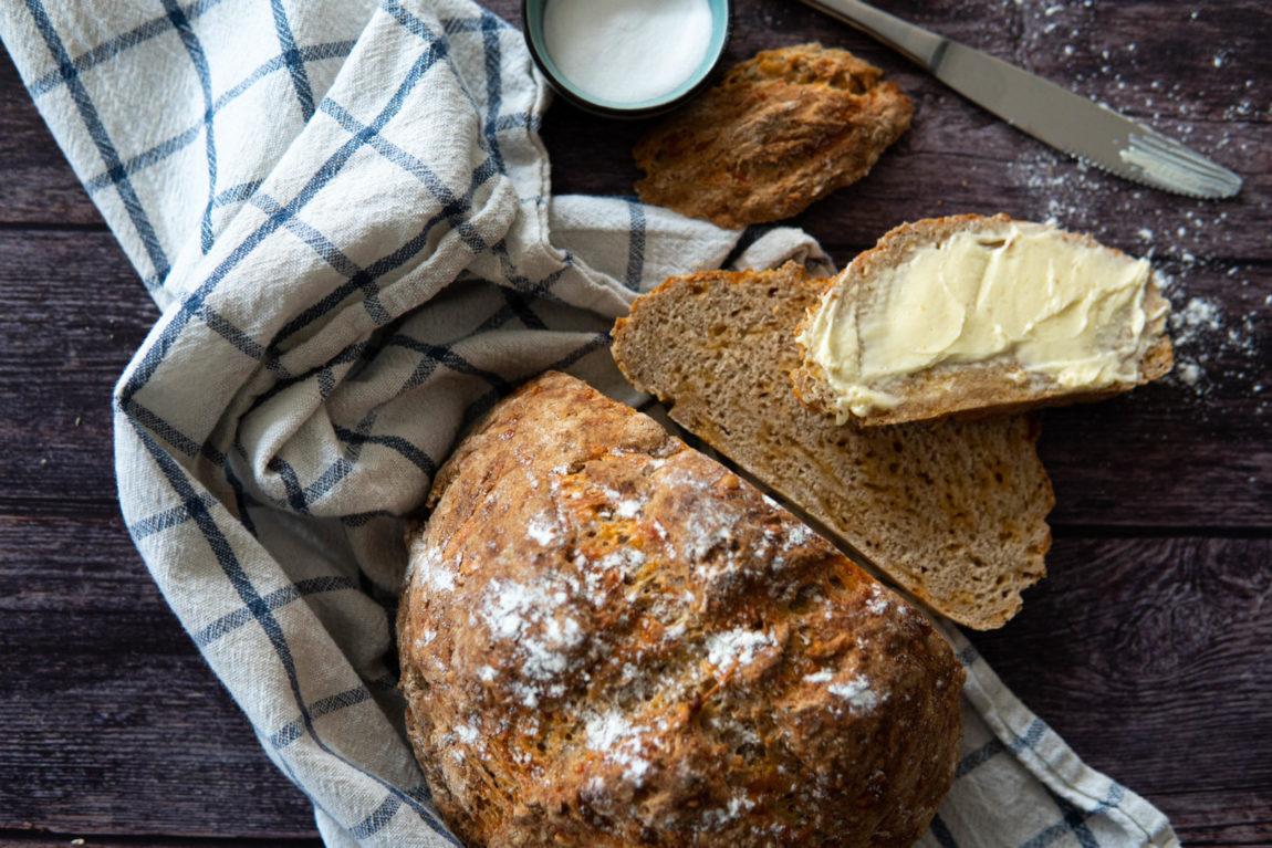 Brot backen mit Natron - Geschnittenes Butterbrot auf blauweißkariertem Küchentuch.