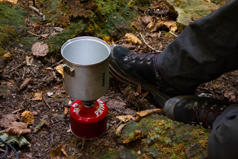 Campingkocher mit heißem Wasser im Wald.